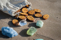Runes on sand. Wood handmade runes and minerals on the sand Stock Images