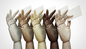 Wood hands of different colors holding business cards Royalty Free Stock Image