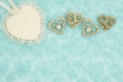 Wood heart with lace and wood hearts on pale teal rose plush fabric background. With muted mix of shades to provide copy-space for your message royalty free stock photography