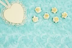 Wood heart with lace on pale teal rose plush fabric background. Wood heart with lace and rose buds on pale teal rose plush fabric background with muted mix of royalty free stock photo