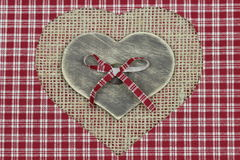 Wood heart on shabby burlap and plaid background Stock Photography