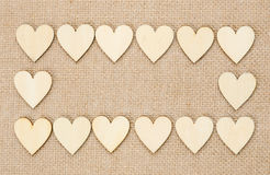 Wood hearts on hessian texture background, valentine background.  Royalty Free Stock Photography