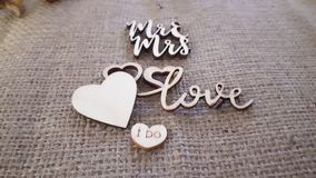 Wood and hessian wedding table decorations. Collection of wooden phrases on hessian to do with weddings. Mr & mrs wooden heart. Love. I do royalty free stock photos