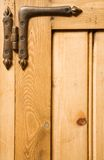 Wood and hinge background. Detail of wooden panelled furniture with iron hinge royalty free stock photography