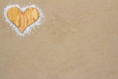 Wood hjärta i sanden. Arkivbild