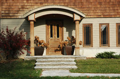 Wood Home Entrance. Home entrance with lots of wood trim and wooden door flanked by two planters with hydrangeas royalty free stock image