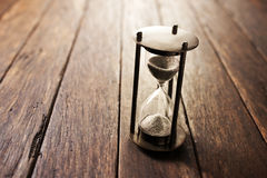 Wood Hourglass Time Background. An hourglass on a wood background Royalty Free Stock Photos