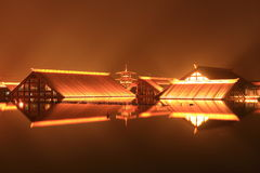 Wood house built on water at night Royalty Free Stock Images