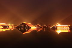 Wood house built on water at night Stock Photo