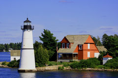 Wood house cottage and lighthouse on the river Royalty Free Stock Photos