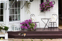 Wood house detail. Entrance of typical swedish wood house , with steps, chairs, and a cat sleeping Royalty Free Stock Images