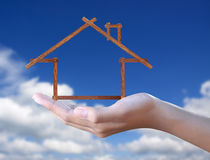 Wood  house in hand on blue sky Royalty Free Stock Images