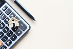 Wood house model and calculator on office desk table royalty free stock image