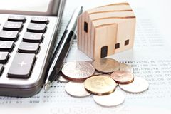 Wood house model, calculator, pen and coins on financial statements or savings account passbook royalty free stock images