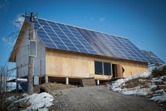 Solar energy. A wood house with solar cell panels covering the entire roof. A renewable energy source Stock Photo