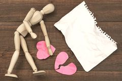 Wood Humane Figure, Torn Paper Page And Broken Hearts. Wood Humane Figurine, Torn Blank Ð¡rumpled Paper Page And Two Broken Hearts On The Wood Background stock image