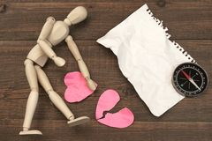 Wood Humane Figure, Torn Paper Page And Broken Hearts. Wood Humane Figurine, Torn Blank Сrumpled Paper Page And Two Broken Hearts On The Wood Background Royalty Free Stock Images
