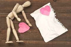 Wood Humane Figurine, Torn Paper Page And Broken Hearts. Wood Humane Figurine, Torn Blank Сrumpled Paper Page And Two Broken Hearts On The Wood Background Stock Images