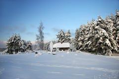 Wood hus i den felika skogen för snö, Lettland Arkivfoton