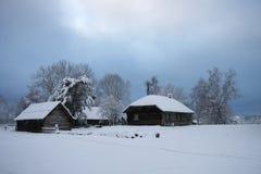 Wood hus i den felika skogen för snö, Lettland Arkivbild