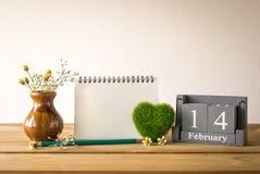 wood kalender för tappning för Februari 14 med grön hjärta, anteckningsbok Royaltyfri Bild
