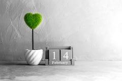 wood kalender för tappning för Februari 14 med grön hjärta på trä t Arkivbild