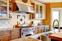 Wood kitchen room with decorated tile backsplash. Yellow tones kitchen with tile decorated backsplash, kitchen appliances royalty free stock photo