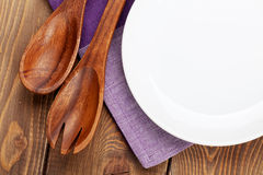 Wood kitchen utensils and empty plate. Over wooden table background with copy space Stock Photos
