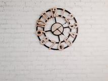 Wood klocka på den vita tegelstenväggen Arkivbilder
