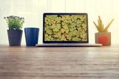 Wood kontorstabell med grön bakgrund för hjärtaformblad på scre arkivbild