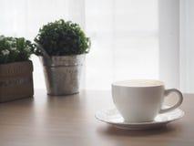 Wood kontorstabell med koppen av lattekaffe och den härliga blomman arkivfoton