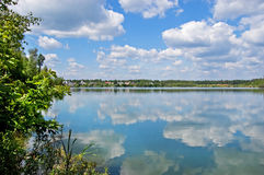Wood lake. Lake with the pure water, surrounded with wood. The  blue sky with white clouds Stock Photo