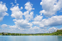 Wood lake. Lake with the pure water, surrounded with wood. The blue sky with white clouds stock photos