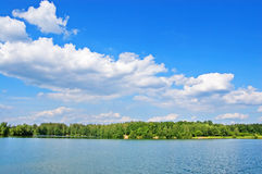 Wood lake. Lake with the pure water, surrounded with wood. The blue sky with white clouds stock photography