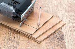 Wood laminate flooring and electric jigsaw Royalty Free Stock Images