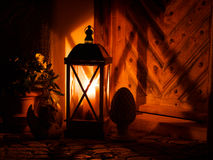 Wood lantern in front of an old door. Wood lantern with burning candle in front of an old door Royalty Free Stock Photos