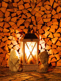 Wood lantern in front of a woodpile. Wood lantern with burning candle in front of a woodpile Stock Image