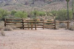 Wood log fence at the start of a hiking trail in the desert royalty free stock photos