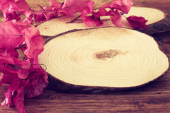 Wood logs and flowers over wooden table Stock Photography