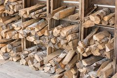 Wood logs are stored in wooden boxes on a wall to dry royalty free stock photos