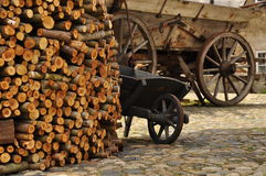 Wood logs and wooden carriage in a cobbled courtyard Royalty Free Stock Photo