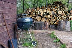 Wood and logs in the yard with tools and a wooden wall Stock Photo
