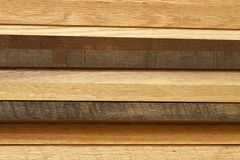 Wood Lumber Stack From The Side. Close-up of various boards of lumber stacked from the side. Most of the lumber here is oak wood in various stages of age and Stock Photography