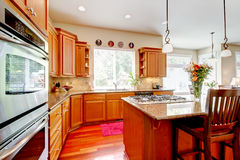 Wood luxury large kitchen with red and granite. Royalty Free Stock Photos