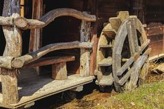 Wood-made objects. Old-time mills with large wheel grinding Royalty Free Stock Image