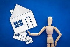 Wood man figure presenting and showing house asset Stock Images
