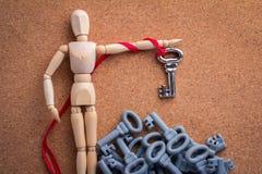 Wood man pick an iron key from the grey keys Stock Image
