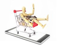 Wood manikin with silver coin in shopping cart on Mobile phone i stock photography
