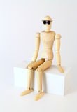 Wood manikin sitting, looking at camera. Stock Photos