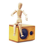 Wood mannequin. Sitting on a speaker isolated on white background Stock Image